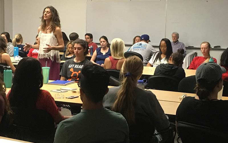 Lucía Duran, a student and meditation instructor, leads her fellow students in a guided meditation at the beginning of class.