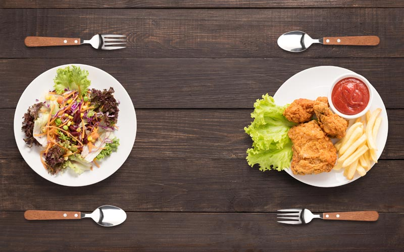 Photograph of two plates of food, to the left a plate of plant based food, to the right a plate of fried foods